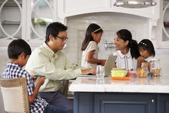 Family At Breakfast Using Digital Devices Stock Photo