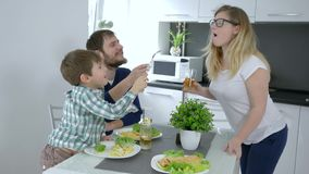 Family breakfast, young Father and son feed mother at same time and laugh indoors. At holiday stock video footage