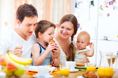 Family breakfast. Young happy family with two kids having breakfast together at home Stock Photos