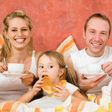 Family breakfasting in bed Stock Photos
