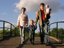 Family on bridge. Evening