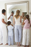 Family Brushing Teeth In Bathroom Mirror Stock Photography