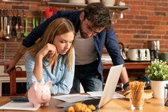 Family budget and finances concept. Family budget and finances. Young women puts a coin into the piggy bank royalty free stock images