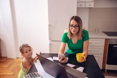 Family budget and finances- single mother with daughter planning. Family budget and finances- young single mother with daughter planning home budget royalty free stock photo