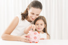 Family budget and savings concept. Mother and daughter putting coins into piggy bank. Junior Savings Account Stock Photography