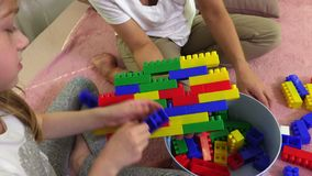 Family build a wall of colorful of play bricks. In room stock video