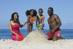 Family building sandcastle on beach, children (5-7) pouring sea water onto sand, smiling, front view Stock Images