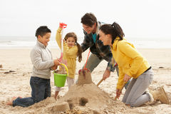 Family Building Sandcastle On Winter Beach. Smiling Stock Photos