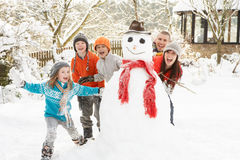 Family Building Snowman In Garden. Family Having Fun Building Snowman In Garden Royalty Free Stock Photography