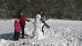 Family Building Snowman In Garden. Two girls wearing gloves on the snowman. Ran the children's parents. mom put on the snowman's scarf and my dad a hat. Happy stock footage