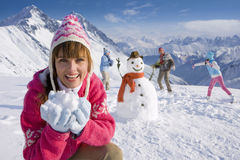 Family building snowman together and having snowball fight stock images