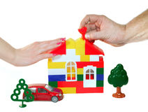 The family builds dream house. Two hands man's and female (or the family) (builds) dreams to construct the house Stock Photo