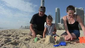 Family builds sand castle in Surfers Paradise Australia stock video