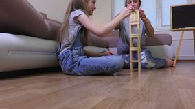 Family builds wooden tower board game stock video footage