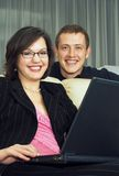 Family business. Business couple of smiling young adults; sitting with a laptop Stock Photo