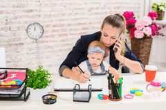 Family Business - telecommute Businesswoman and mother with kid is making a phone call. At the workplace, together with a small child Stock Photos