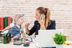 Family Business - telecommute Businesswoman and mother with kid is making a phone call. At the workplace, together with a small child Royalty Free Stock Photo