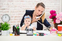 Family Business - telecommute Businesswoman and mother with kid is making a phone call. At the workplace, together with a small child Stock Image