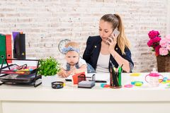 Family Business - telecommute Businesswoman and mother with kid is making a phone call. At the workplace, together with a small child Royalty Free Stock Images