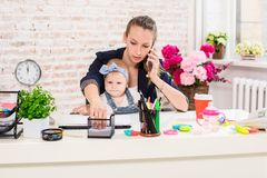 Family Business - telecommute Businesswoman and mother with kid is making a phone call. At the workplace, together with a small child Stock Photography