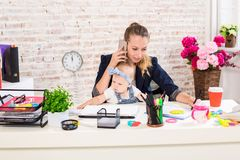 Family Business - telecommute Businesswoman and mother with kid is making a phone call. At the workplace, together with a small child Royalty Free Stock Photos