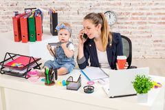Family Business - telecommute Businesswoman and mother with kid is making a phone call. At the workplace, together with a small child Royalty Free Stock Image
