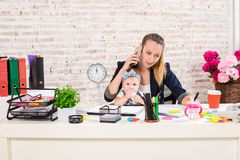 Family Business - telecommute Businesswoman and mother with kid is making a phone call. At the workplace, together with a small child Stock Photo