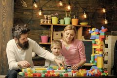 Family on busy face spend time together in playroom. Educational game concept. Father, mother and cute son play with. Constructor bricks. Kid with parents play stock images