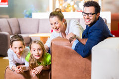 Family buying couch in furniture store. Family selecting together sofa in home-centre to furniture store Royalty Free Stock Photography