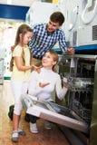Family buying dishwashing machine Royalty Free Stock Image