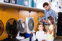 Family buying fan blower. Cheerful men and women with girl buying fan blower in store with electronics. Focus on woman Royalty Free Stock Image