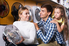 Family buying fan blower. Smiling men and women with girl buying fan blower in store with electronics. Focus on woman stock photos