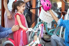 Family buying helmet for bicycle for a girl in a bicycle store. Family buying helmet for bicycle for a happy girl in a bicycle store royalty free stock images