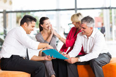 Family buying new car. Happy family buying a new car at vehicle showroom Stock Image