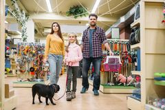 Family buying supplies for puppy in pet shop Royalty Free Stock Photos