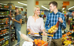 Family  buying sweet fruits. Family couple 25s buying sweet fruits in local food shop Royalty Free Stock Photos