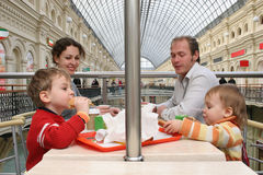 Family in a cafe. In a big shop with food and drinks Stock Image