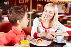 Family in cafe. Portrait of cute lad and his mother in cafe Royalty Free Stock Photography