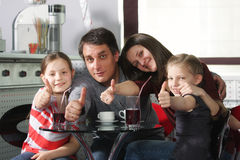 Family in cafe showing thumbs up. Happy family sitting in cafe at glass table showing thumbs up Royalty Free Stock Photos