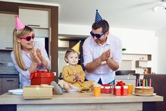 A family with a cake congratulates a happy child on his birthday stock images