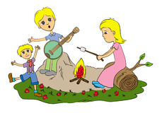 Family camp fire. A very happy family having a camp fire while dad plays the banjo Royalty Free Stock Photography