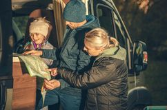 Family Camper Trip Planning. Young Caucasian Family Taking Look on the Map in the RV Motorhome Side Doors stock photo
