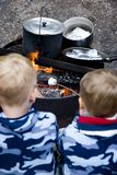 Family camping. Boys from family camping and roasting marshmallows over campfire royalty free stock photography