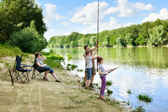 Family camping and fishing, people active in nature, child caugh. T fish on bait, river and forest, summer season royalty free stock images
