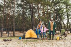 young happy family camping in forest on rainy royalty free stock photo