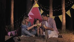 Family camping, joyful mom and dad with beautiful daughter have fun at night picnic in forest eat bananas and laugh. Against a wigwam stock video footage