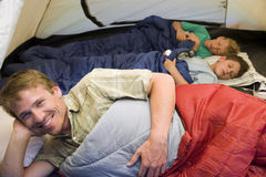 Family camping in tent, children (8-10) sleeping in background, focus on father resting in sleeping bag in foreground, smiling, po Stock Photography