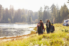 Family on camping trip walk near lake, looking at each other royalty free stock images