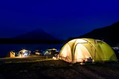 Family camping vacation at Lake Shoji. Camping at Lake Shoji with mount fuji view with blue sky at night, Yamanashi Prefecture, Japan. Vacation trip with copy stock image