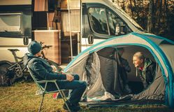 Family Camping Vacation. Motorhome and Tent on the Campsite. Caucasian Family royalty free stock photography